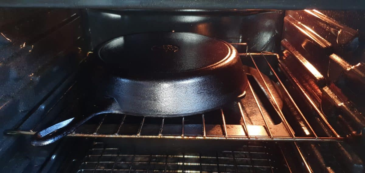 a cast iron pan upside down in the oven as part of the seasoning process