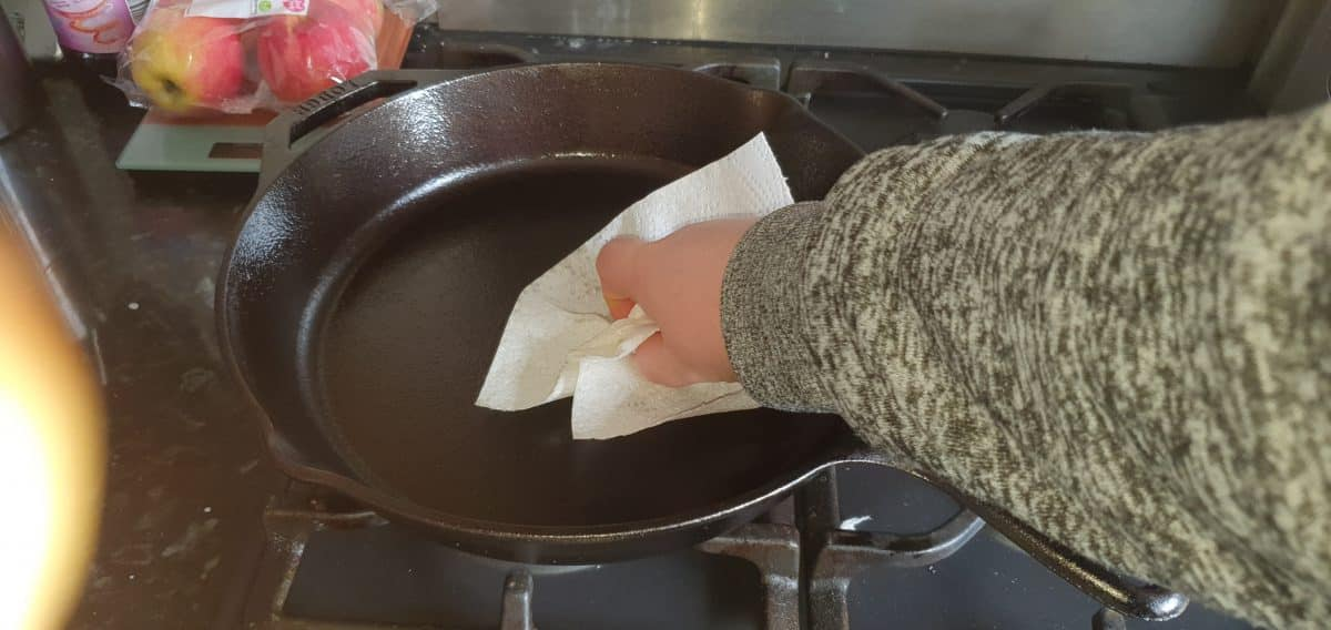 using a paper towel to rub in the flax seed oil for seasoning the cast iron